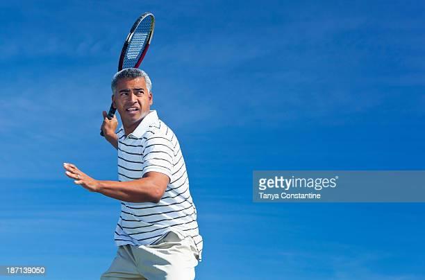 Mixed race man playing tennis outdoors