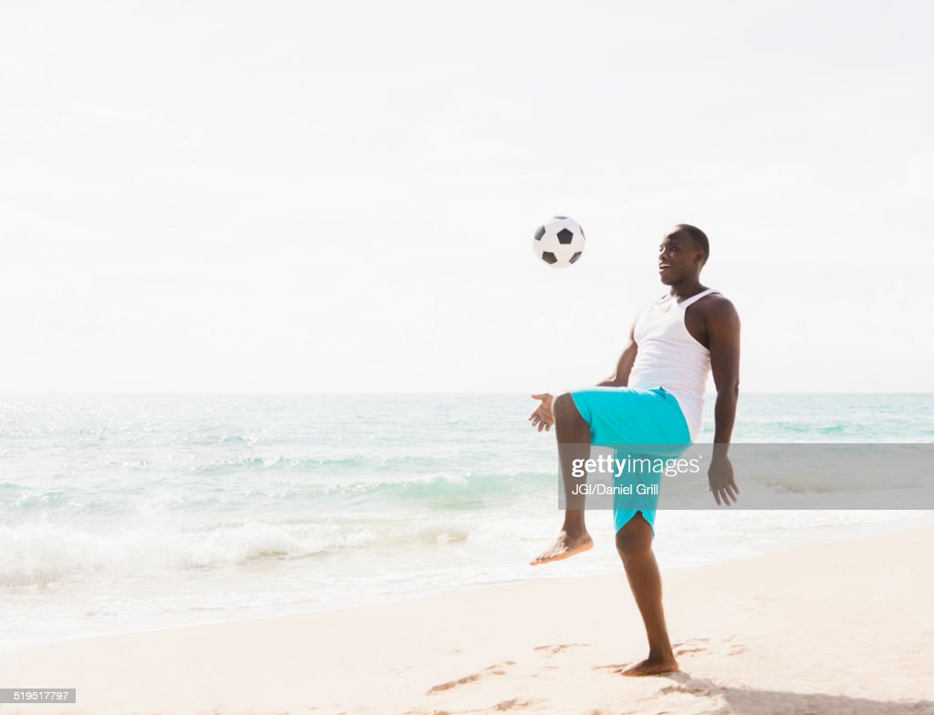 Mixed race man playing with soccer ball on beach : Stock Photo