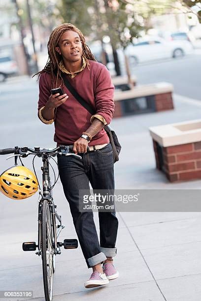 Mixed race man pushing bicycle outdoors
