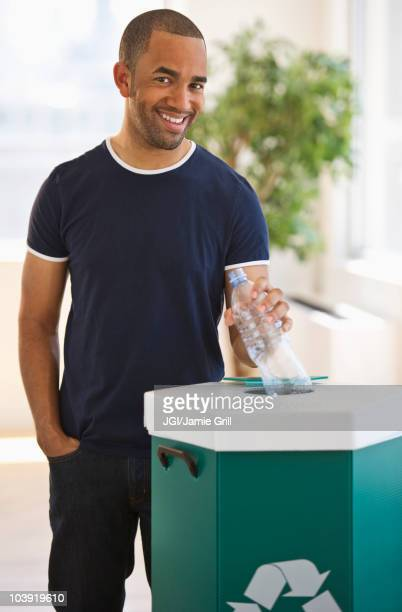 mixed race man putting plastic bottle in recycling bin - putting stock pictures, royalty-free photos & images