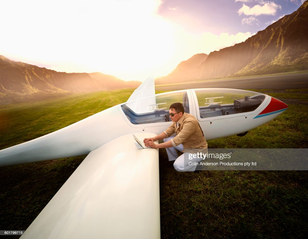 Mixed race man reading map on glider airplane : Stock Photo