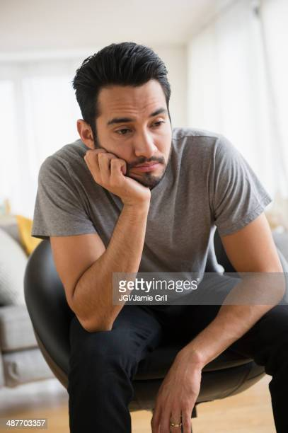 mixed race man resting chin in hand - disappointment stock pictures, royalty-free photos & images