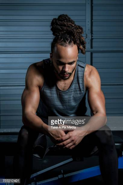 Mixed Race man resting in gymnasium
