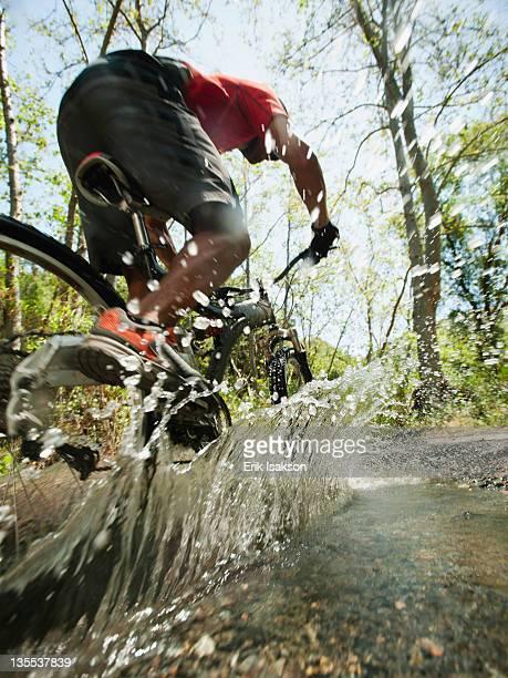 mixed race man riding mountain bike through stream - マウンテンバイキング ストックフォトと画像