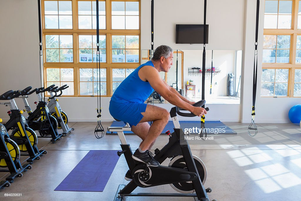 Mixed Race man riding stationary bicycle in gymnasium : Stock Photo