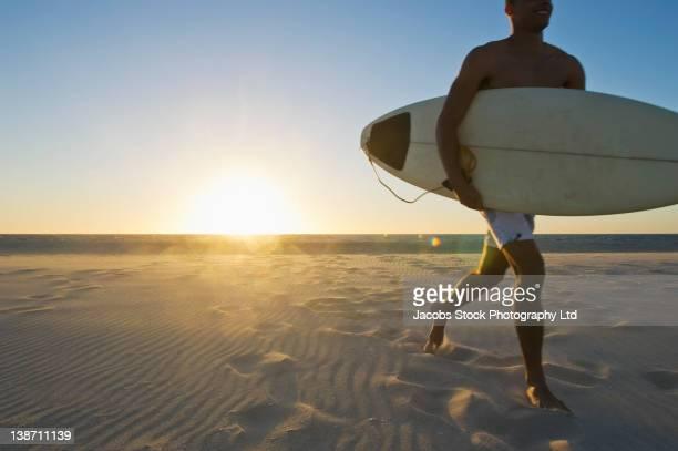 Mixed race man running on beach with surfboard