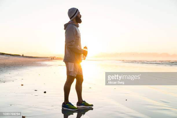 mixed race man running on the beach at dawn - one man only stock pictures, royalty-free photos & images
