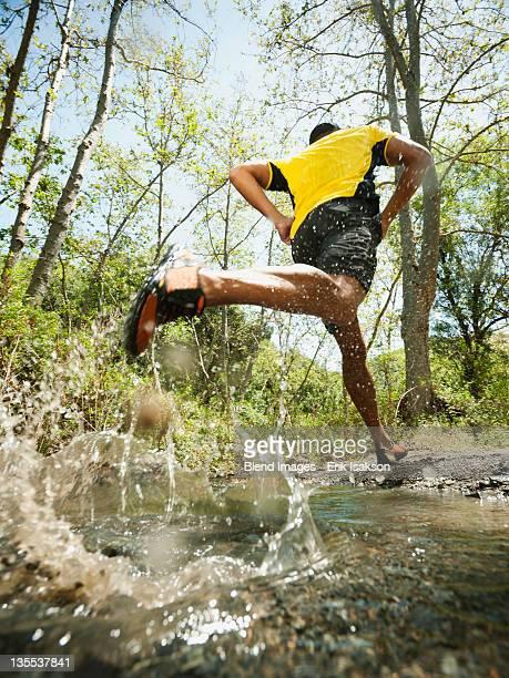 Mixed race man running through stream