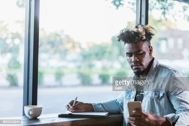 Mixed race man sitting by window in coffee shop, writing