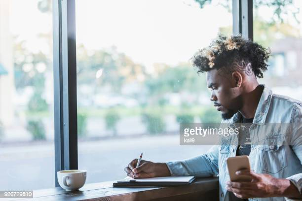mixed race man sitting by window in coffee shop, writing - handsome native american men stock pictures, royalty-free photos & images