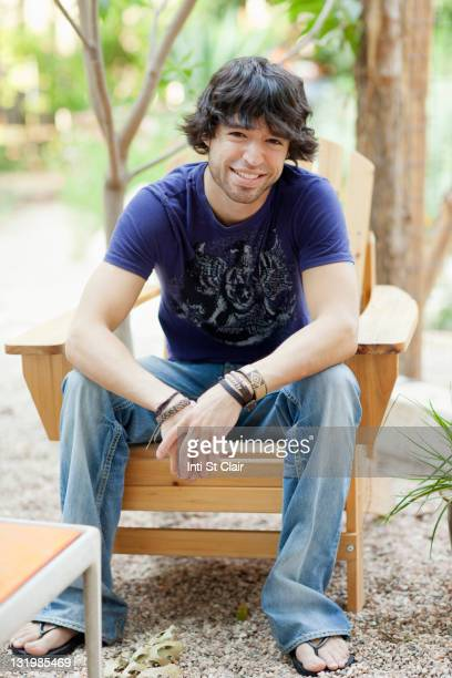 Mixed race man sitting in Adirondack chair