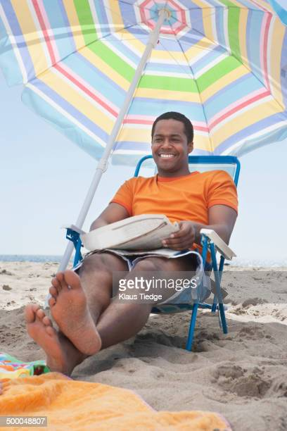 mixed race man sitting in lawn chair on beach - barefoot black men stock pictures, royalty-free photos & images