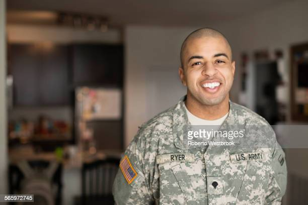 mixed race man smiling in living room - army soldier stock pictures, royalty-free photos & images