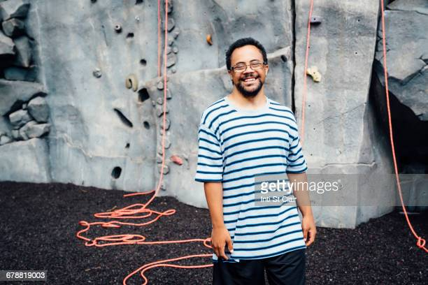 Mixed Race man smiling near rock climbing wall