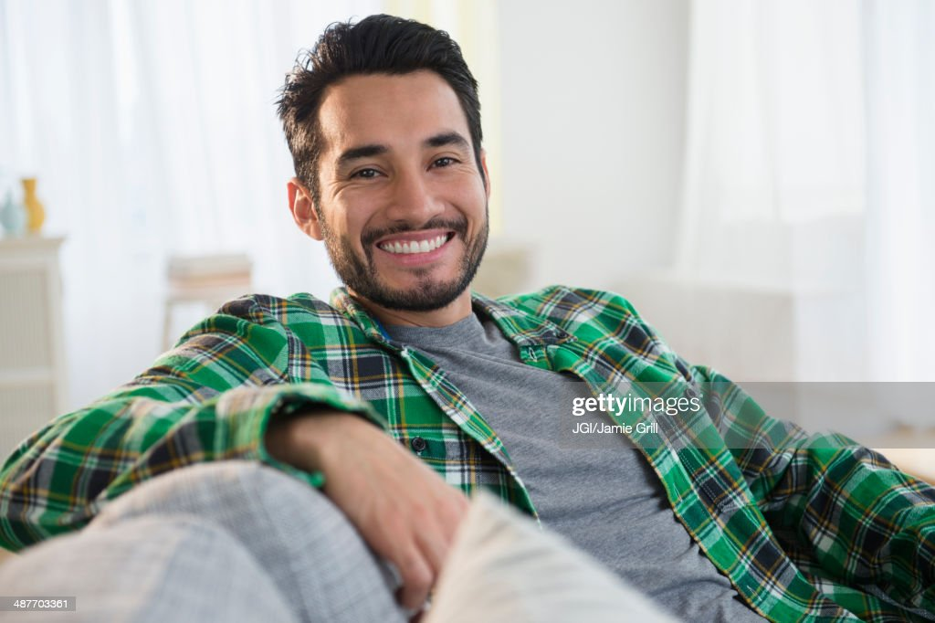 Mixed race man smiling on sofa : Stock Photo
