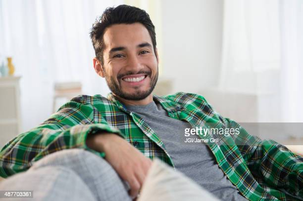 Mixed race man smiling on sofa