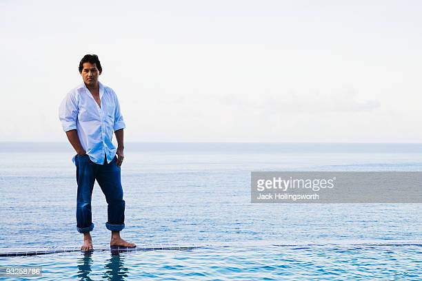 mixed race man standing on edge of infinity pool - rolled up trousers stock pictures, royalty-free photos & images