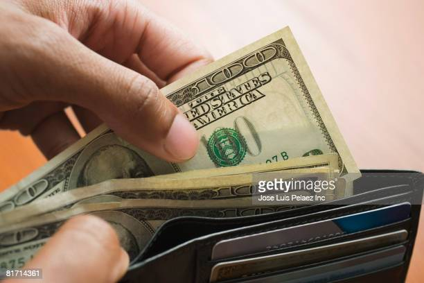 mixed race man taking money out of wallet - american one hundred dollar bill stock pictures, royalty-free photos & images