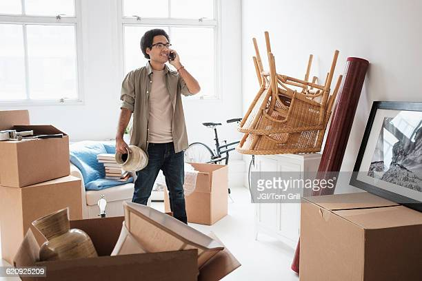 Mixed race man unpacking in new home