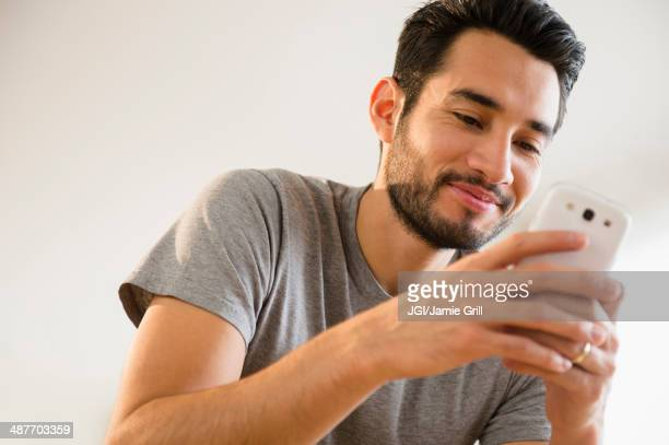 Mixed race man using cell phone