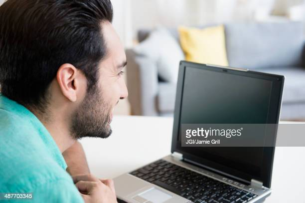 Mixed race man using laptop