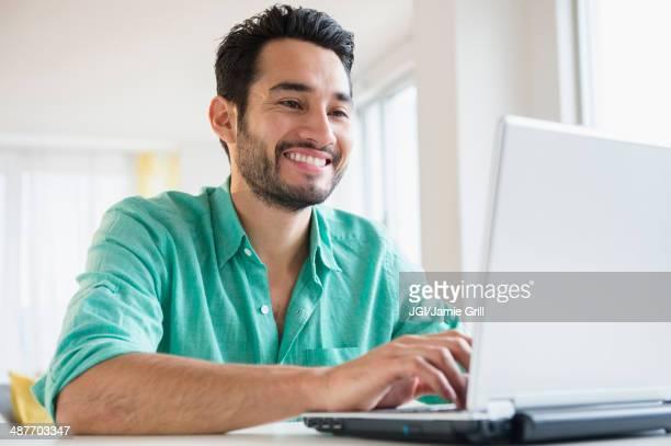 mixed race man using laptop - solo un uomo di età media foto e immagini stock