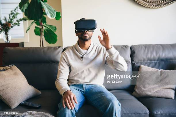 Mixed race man using virtual reality goggles