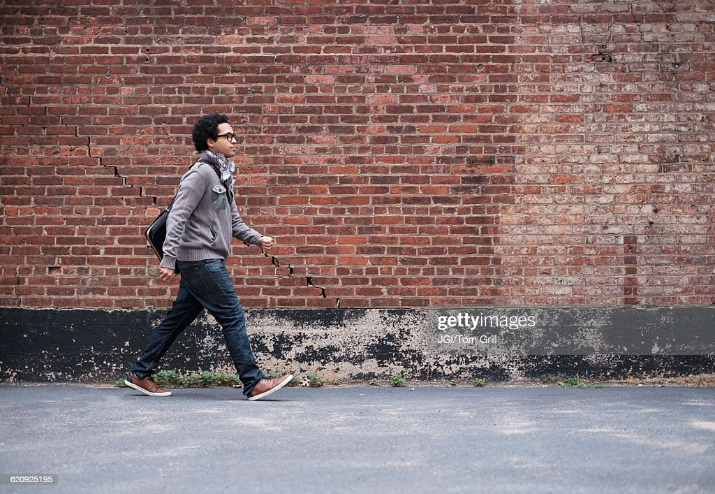 Mixed race man walking near brick wall : Stock Photo
