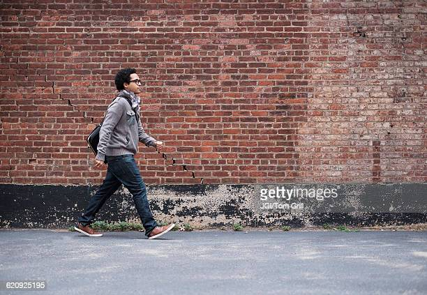 Mixed race man walking near brick wall