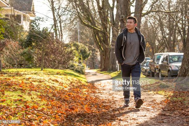Mixed race man walking on suburban street