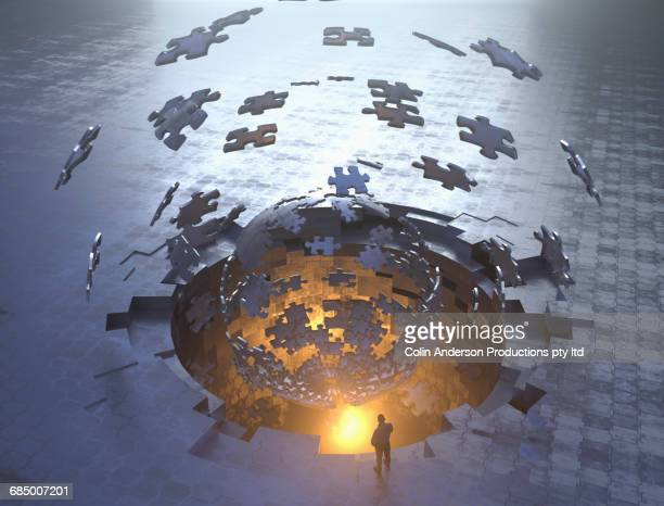 Mixed Race man watching jigsaw puzzle piece sphere floating over hole