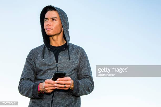 mixed race man wearing hoody texting on cell phone - sportswear stock pictures, royalty-free photos & images