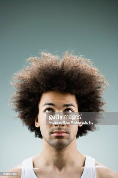 Mixed Race man with afro looking up