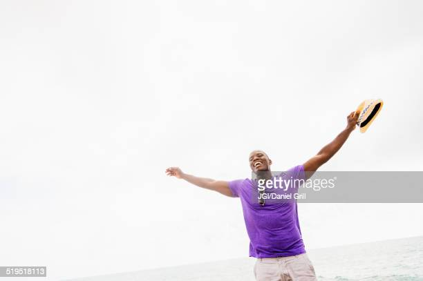 Mixed race man with arms outstretched on beach