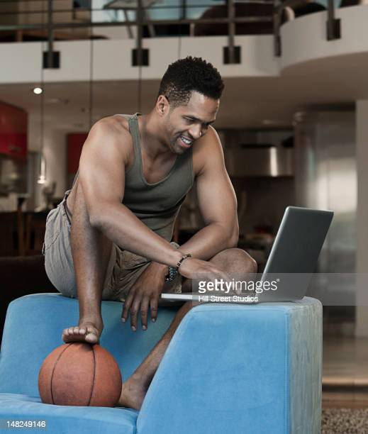 Mixed race man with basketball using laptop in living room