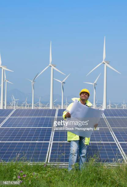 Mixed race man with blueprints near solar panels and wind turbines