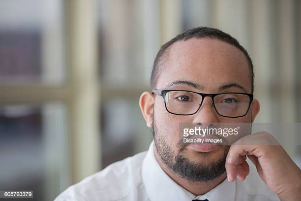 mixed race man with down syndrome resting chin in hands - intellectually disabled stock pictures, royalty-free photos & images