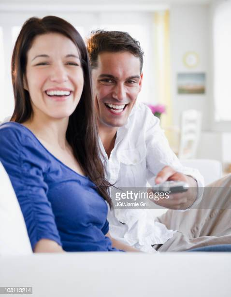 Mixed race man with remote control watching television with wife