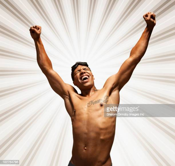 Mixed race man with tattoo and swimming goggles, cheering