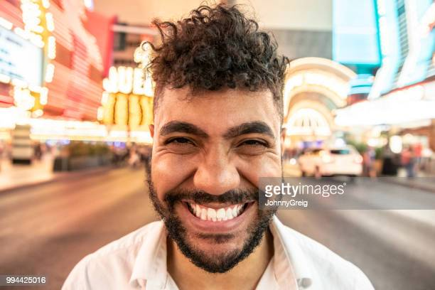 mixed race man with toothy grin facing camera - wide angle stock pictures, royalty-free photos & images