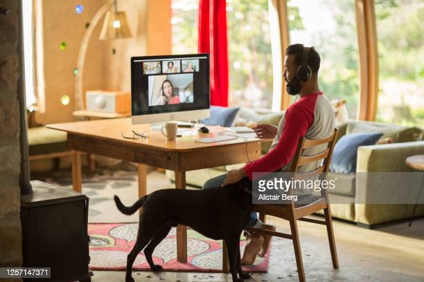mixed race man working from home on his computer during lockdown - working from home stock pictures, royalty-free photos & images