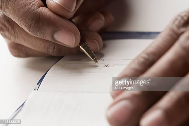 Mixed race man writing a check