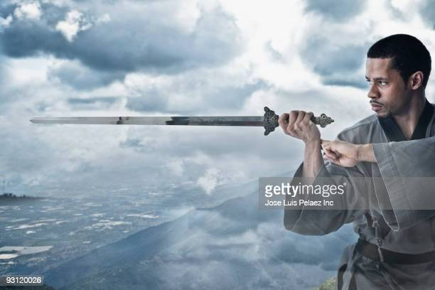 Mixed race martial artist holding sword on cliff