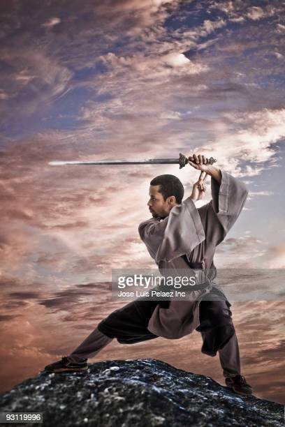 Mixed race martial artist holding sword on rock