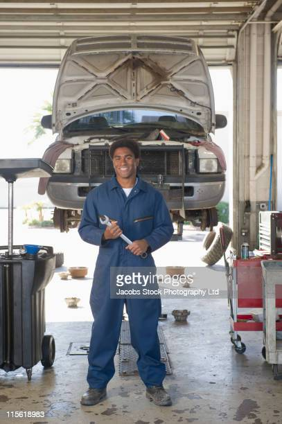 mixed race mechanic working in auto repair shop - black jumpsuit stock photos and pictures