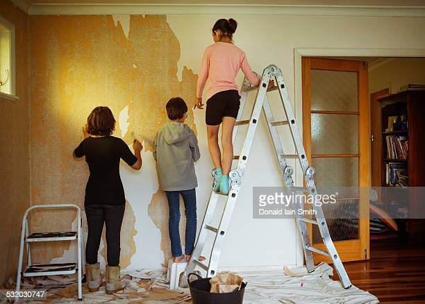Mixed race mother and children stripping wallpaper in living room