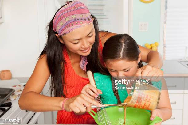 Mixed race mother and daughter baking in kitchen