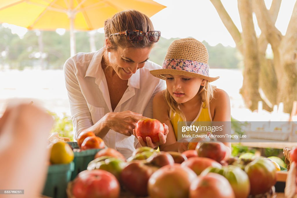 Mixed race mother and daughter browsing produce at farmers market : Foto stock