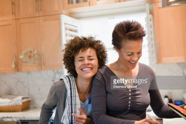 Mixed race mother and daughter cooking in kitchen