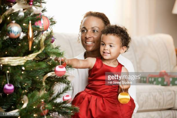 Mixed race mother and daughter decorating Christmas tree